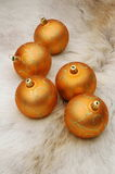 Decorated golden Christmas balls. On reindeer fur coat stock photos