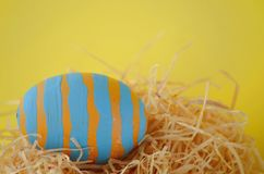 Decorated hand painted blue striped Easter egg in a straw nest on bright yellow background with copy space Stock Photography