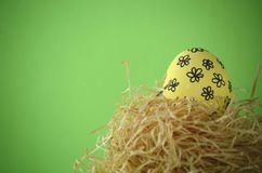 Decorated handpainted yellow floral Easter egg in a straw nest against bright yellow background with copy space. Decorated hand painted yellow floral Easter egg Stock Photo