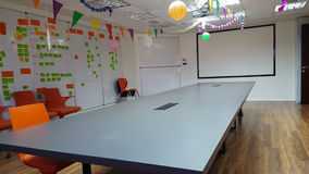 Decorated for holiday business meeting room. With agile board fully sticked, big table, screen, desk, projector, garlands and colored lamps Stock Image
