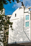 Decorated house wall. A white building wall with the shadow of near tree painted on it Stock Images