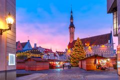 Christmas Market in Tallinn, Estonia. Decorated and illuminated Christmas tree and Christmas Market at Town Hall Square or Raekoja plats at beautiful sunrise royalty free stock images
