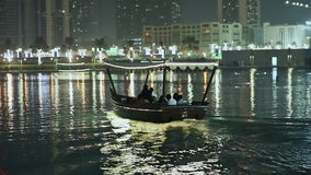 Decorated with lanterns boat floats with people. Dubai. stock video