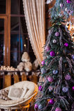 Decorated lilac Christmas tree in Rural wooden living room Royalty Free Stock Image