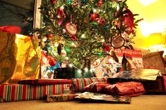 Decorated lit and glowing Christmas tree with gift-wrapped boxes and presents under it. Cozy and festive, holiday living room. Decorated lit and glowing Stock Images
