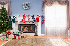 Decorated living room at home for Christmas. With colorful stockings on the mantelpiece, heap of gift wrapped presents and Xmas tree, copy space on lace Royalty Free Stock Photos