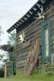 Decorated log cabin. Old alaskan log cabin with antlers and wheel as decorations Stock Photo