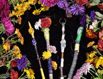 Decorated magic wands in circle of flowers, top view. Occult, esoteric, divination and wicca concept. Halloween vintage background stock photo