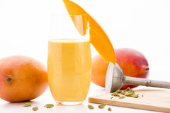 Decorated Mango Lassie, Cardamom And Two Mangos. Mango lassi in a glass decorated with a cut mango fruit chip. Two entire mangos and cardamon seeds, some crushed royalty free stock image