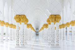 Decorated marble columns on the top with like golden palm in corridor without people inside Sheikh Zayed Grand Mosque. In the morning at Abu Dhabi, UAE Royalty Free Stock Photography