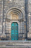 Decorated old door. Ancient door with decoration. Decorated entrance into old historic building made in romanesque revival style. Arch and columns are used as Stock Image