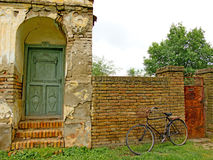 Decorated old green door, staircase of red bricks and old, black bike Stock Photography