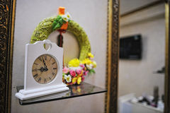 Decorated old vintage clock near mirrors at make up saloon Stock Photo