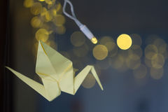 Decorated origami cranes on xmas background. Paper yellow crane origami on a dark Christmas background garland Stock Image
