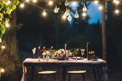 Decorated outdoor wedding table with flowers in rustic style. Decorated outdoor wedding table with flowers, lights and candles in rustic style Stock Image