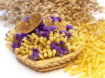 Decorated pasta. Yellow pasta and flowers in the basket royalty free stock photo
