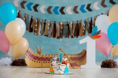 Decorated photo zone for 1 year Indian Apache chief with a canoe for a children`s party. First birthday and smash cake royalty free stock images