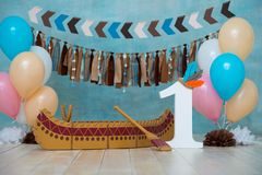 Decorated photo zone for 1 year Indian Apache chief with a canoe for a children`s party. First birthday and smash cake stock photos