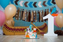 Decorated photo zone for 1 year Indian Apache chief with a canoe for a children`s party. First birthday and smash cake stock photo