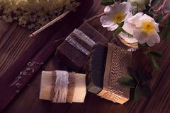 Decorated pieces of various dry soap with an aroma-stick, roses. And white elder on a wooden background Stock Photography