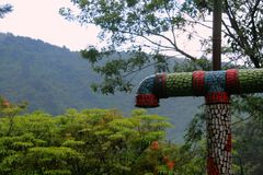 Decorated pipe at mountain resort, Apaneca, El Salvador. Decoration includes ceramic shreds of red, green and blue color. Mountain and forest at the background stock photos