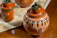 Decorated pottery jar on a table with embroidered mat Royalty Free Stock Photos