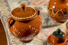 Decorated pottery sugar bowl on a table with embroidered mat Royalty Free Stock Images