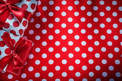 Decorated presents on polka-dot red table cloth celebrations con Stock Images