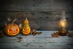 Decorated pumpkins for a Halloween on a mystical autumn background with gas lamp stock photos