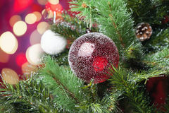 Decorated red ball on Christmas tree with bokeh at background Stock Photography