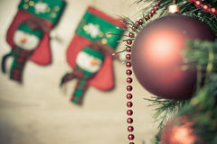Decorated red ball on Christmas tree with socks at background Stock Image