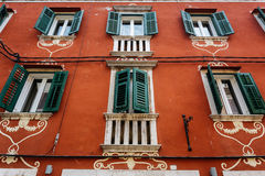 A decorated red house facade with green shutters on the windows in Rovinj, Croatia. Royalty Free Stock Photography