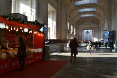 Decorated with red kiosks large corridor of the Milan Central railway station and people walking. stock photos