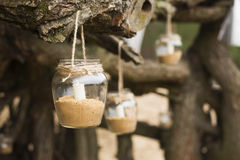 Decorated romantic place for a date with jars full of candles hunging on tree. Copy Space Royalty Free Stock Image