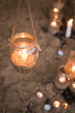 Decorated romantic place for a date with jars full of candles hunging on tree and standing on a sand Royalty Free Stock Photography