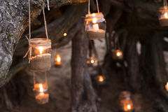 Decorated romantic place for a date with jars full of candles hunging on tree and standing on a sand. Copy Space Royalty Free Stock Photo