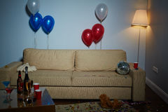 Decorated room. Empty room with couch, lamp, balloons, disco-ball, teddybears and drinks after party Royalty Free Stock Image