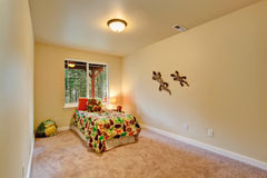 Decorated room for kids. Simple room for kids with single bed, toys and decorated wall Royalty Free Stock Photo