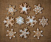 Decorated snowflake gingerbreads. Decorated snowflake Christmas gingerbread cookies on brown burlap canvas background stock photography