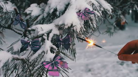 Decorated snowy forest tree with lilac ribbons and Bengal fire in a female hand. Decorations on the Christmas. Winter on the tree in the snow hang the Christmas stock video footage
