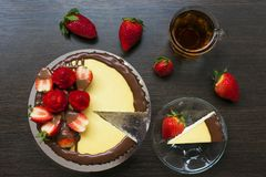 Decorated strawberry cheesecake with a cup of tea and strawberries stock photos