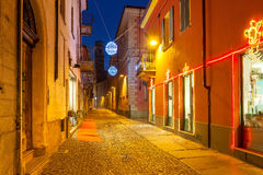 Decorated street of Alba in the evenig. Narrow cobbled street among houses illuminated and decorated for Christmas and New Year holidays in town of Alba Stock Photos
