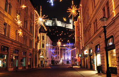 Decorated street in Ljubljanas old city centre for Christmas and New Years holiday, with Ljubljanas castle raising above Stock Photos