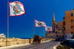 Decorated street in old town of Valletta, Malta. Festively decorated street with flags of all the Grand Masters of the Sovereign Military Order of Malta in the Royalty Free Stock Image