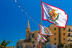 Decorated street in old town of Valletta, Malta. Festively decorated street with flags of all the Grand Masters of the Sovereign Military Order of Malta in the Stock Photo