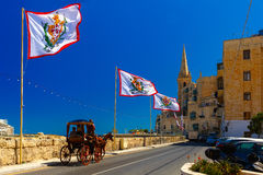 Decorated street in old town of Valletta, Malta. Festively decorated street with flags of all the Grand Masters of the Sovereign Military Order of Malta in the Stock Photography