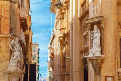 Decorated street in old town of Valletta, Malta. The traditional Maltese street stairs with corners of houses, decorated with statues of saint and Our Lady in Stock Images
