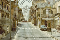 Decorated street in Valletta city. Malta. City street with decoration. Delicate openwork decoration outside in harmony with openwork architecture of houses Stock Photos