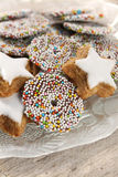 Decorated sugar cookies. Christmas cookies decorated with confetti and glaze on a glass plate Royalty Free Stock Photography
