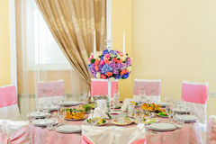 Decorated table with beautiful flowers and a lot of dishes in the restaurant Royalty Free Stock Images